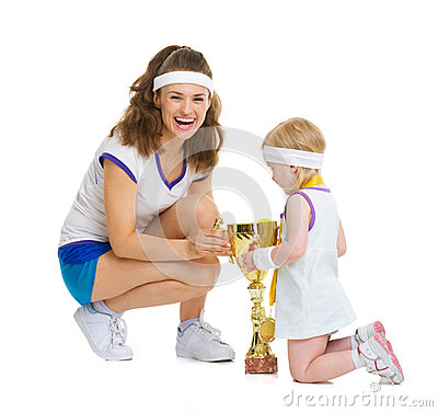 Happy mother and baby in tennis clothes with medal and goblet