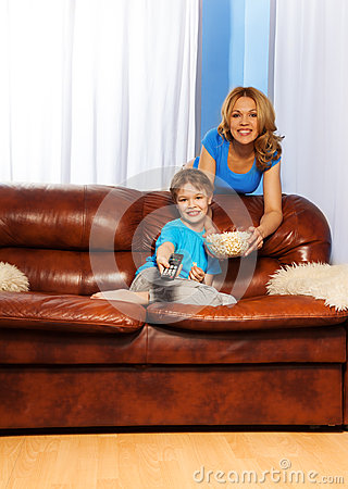 Happy mother and boy watching TV program together