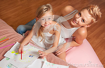 Happy mother and daughter drawing and having fun