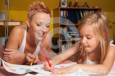 Happy mother and daughter drawing at their home