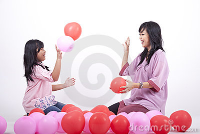 Happy Mother and Daughter play with balloon