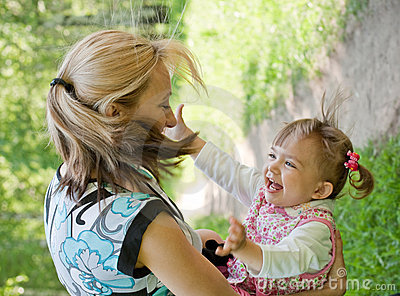 Happy mother and daughter playing outdoor, Summer