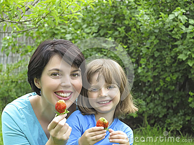 Happy mother and her daughter eating strawberries