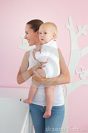 Happy mother holding cute baby in bedroom