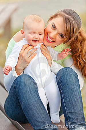 Happy mother holding smiling adorable baby girl