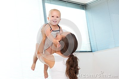 Happy mother lifting up cute baby at home