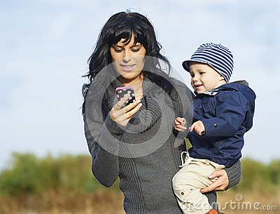 Happy mother with little boy on cellphone