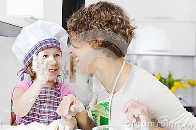 Mother with daughter joyful cooking
