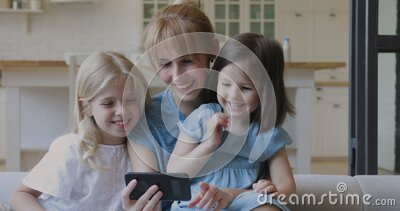 Happy mother and little daughters laughing watching cartoons on smartphone stock video