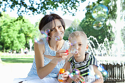 Happy mother and little son with soap bubbles outdoors