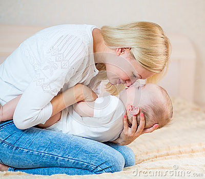 Happy mother playing with baby boy indoors