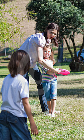 Happy mother playing Frisbee with her children