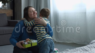 Cute son giving gift box to mom on Mother`s Day stock video footage