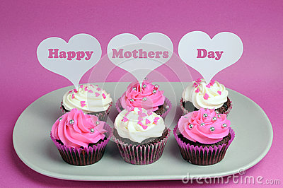 Happy Mother s Day message across white heart toppers on pink and white decorated red velvet cupcakes