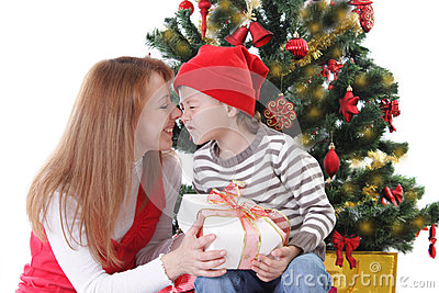 Happy mother and son having fun under Christmas tree