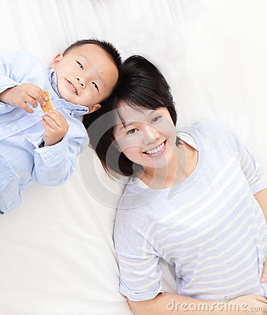 Happy mother and son lying on bed