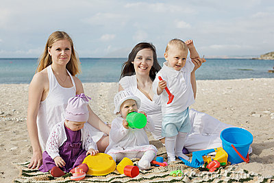 Happy mothers with children at the beach