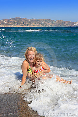 Happy mum with  daughter have  rest on the sea