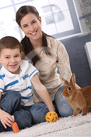 Happy mum and little son playing with rabbit