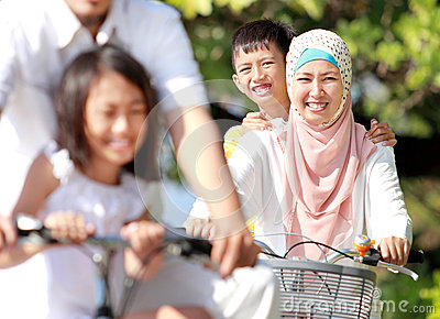 Happy muslim family riding bikes