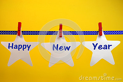 Happy New Year message greeting written across white stars and red pegs on blue polka dot ribbon hanging from pegs on a line