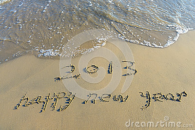 Happy new year written in beach