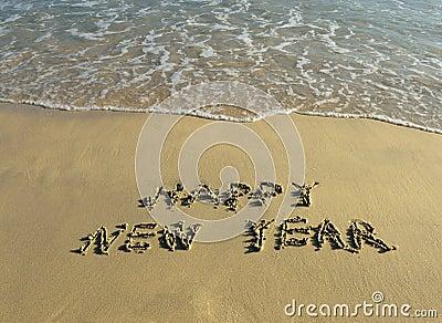 Happy new year written in beach