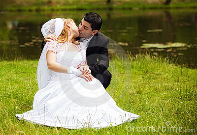 Happy newlyweds on grass in park