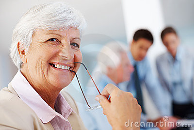Happy old businesswoman holding glasses in mouth