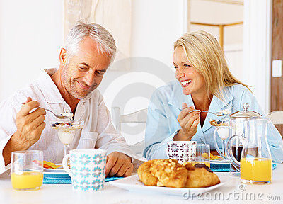 Happy old couple having breakfast at the table