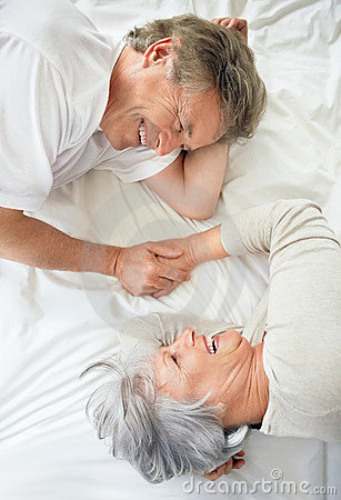 Happy old couple holding hands in bed
