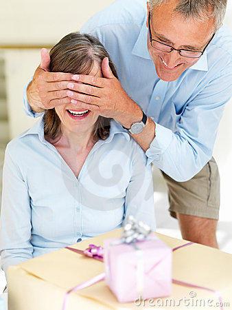 Happy old man closing eyes of his wife with gifts