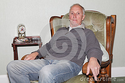 Happy old man sitting in his armchair