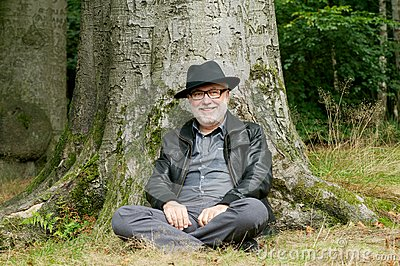 Happy old man sitting under tree in the forest
