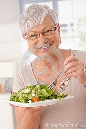Happy old woman eating green salad