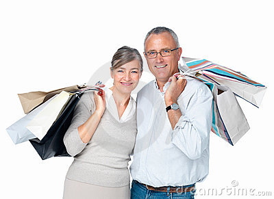 Happy older couple standing carrying bags