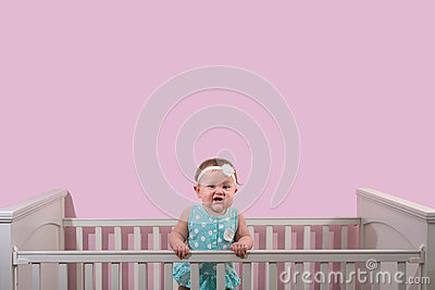 Happy one year old girl standing in her crib wearing polka dots Stock Photo