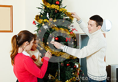 Happy parents and child decorating Christmas tree