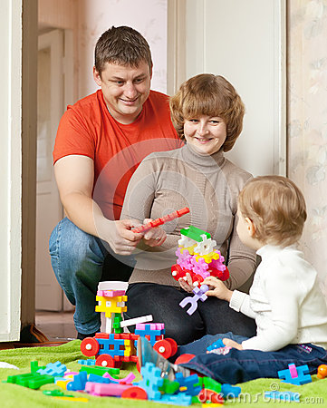 Happy parents and child plays with meccano