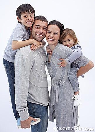 Happy parents giving children piggyback rides