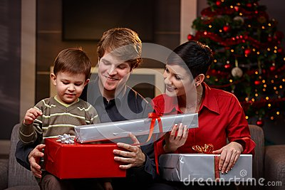 Happy parents giving christmas gifts to son