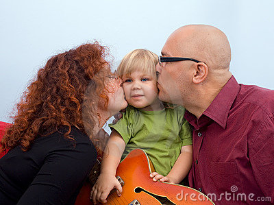 Happy parents kissing daughter