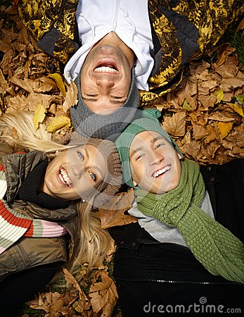 Happy people in autumn park laying among leaves