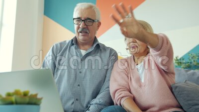 Happy people married couple enjoying online video call with laptop at home. Happy people married couple is enjoying online video call talking waving hand stock footage