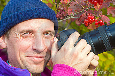 Happy photographer on arrowwood bush background