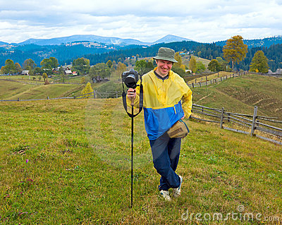 Happy photographer on autumn mountain background
