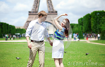 Happy positive couple dancing near the Eiffel tower