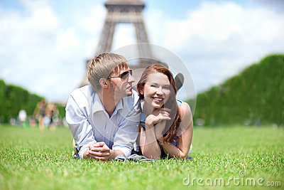 Happy positive couple laying on the grass in Paris