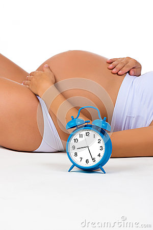 Free Happy Pregnancy. Pregnant Belly With Alarm Clock. Soon Birth. Fetal Development By Months Stock Image - 65251821