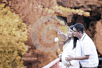 Happy pregnant couple in autumn